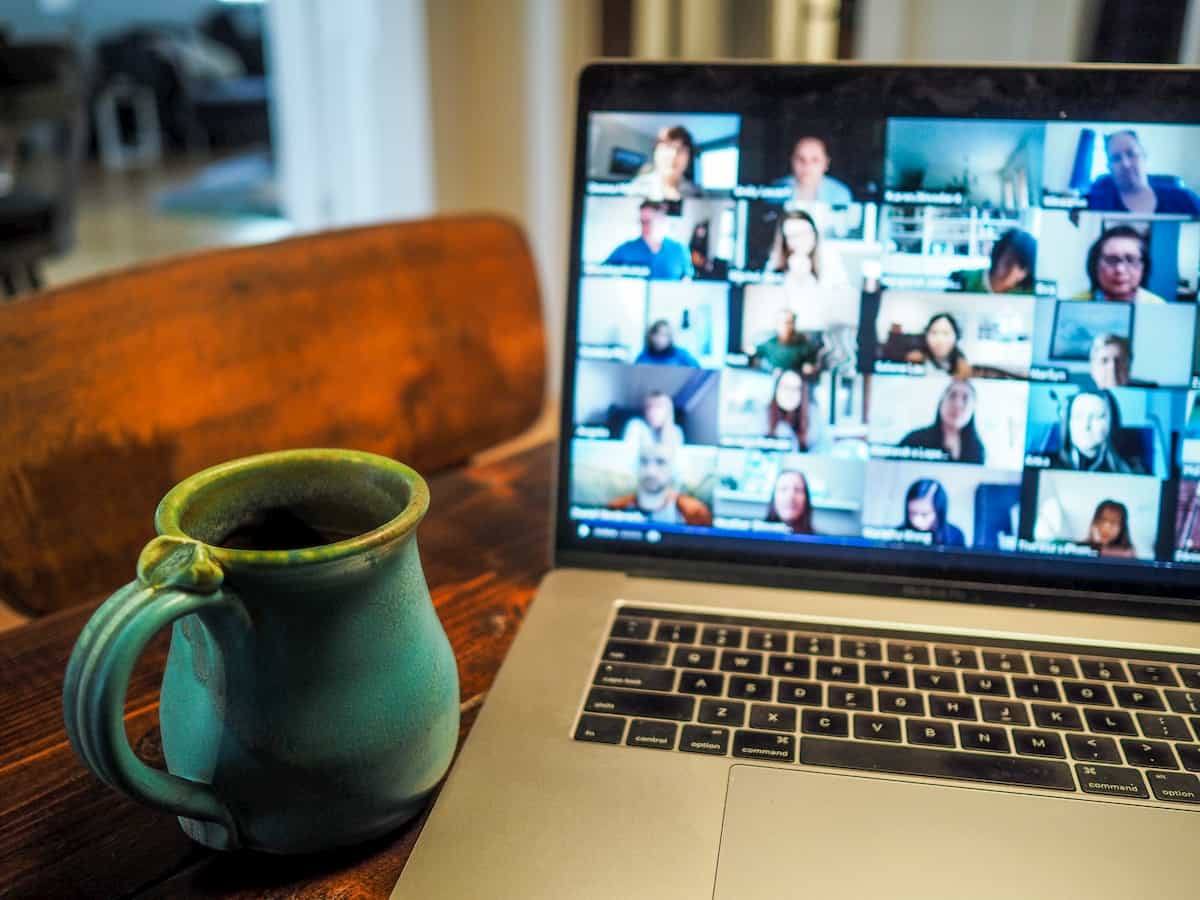 A video conference on a laptop and a maroon coffee mug next to laptop