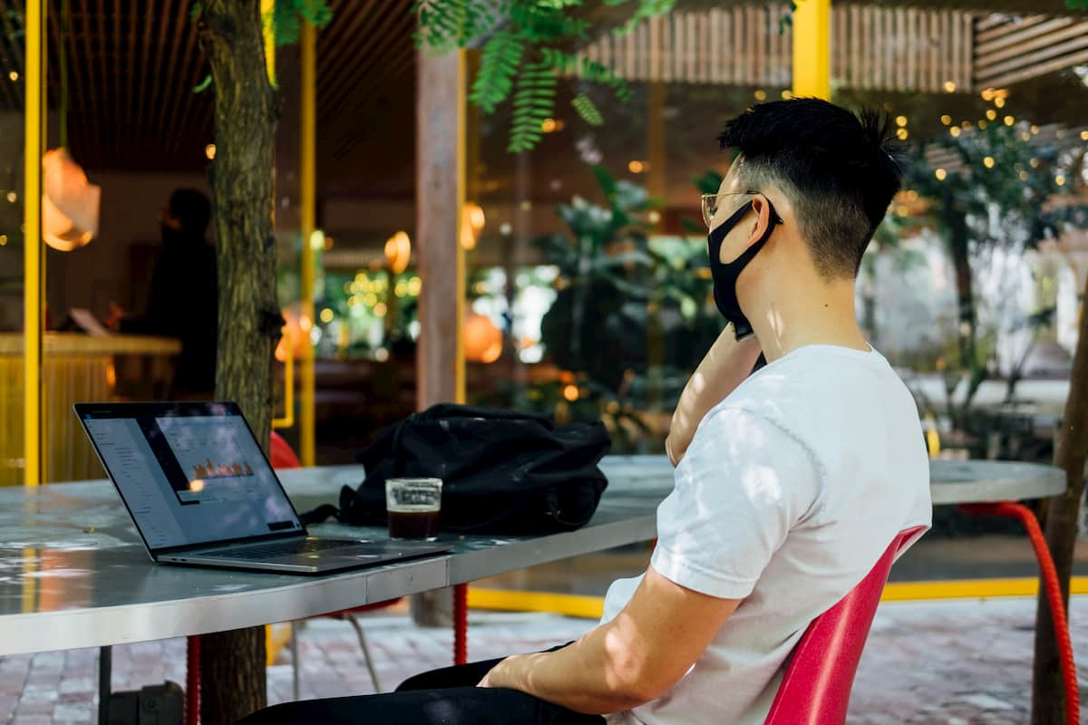 Man wearing a mask sitting in a cafe with a laptop