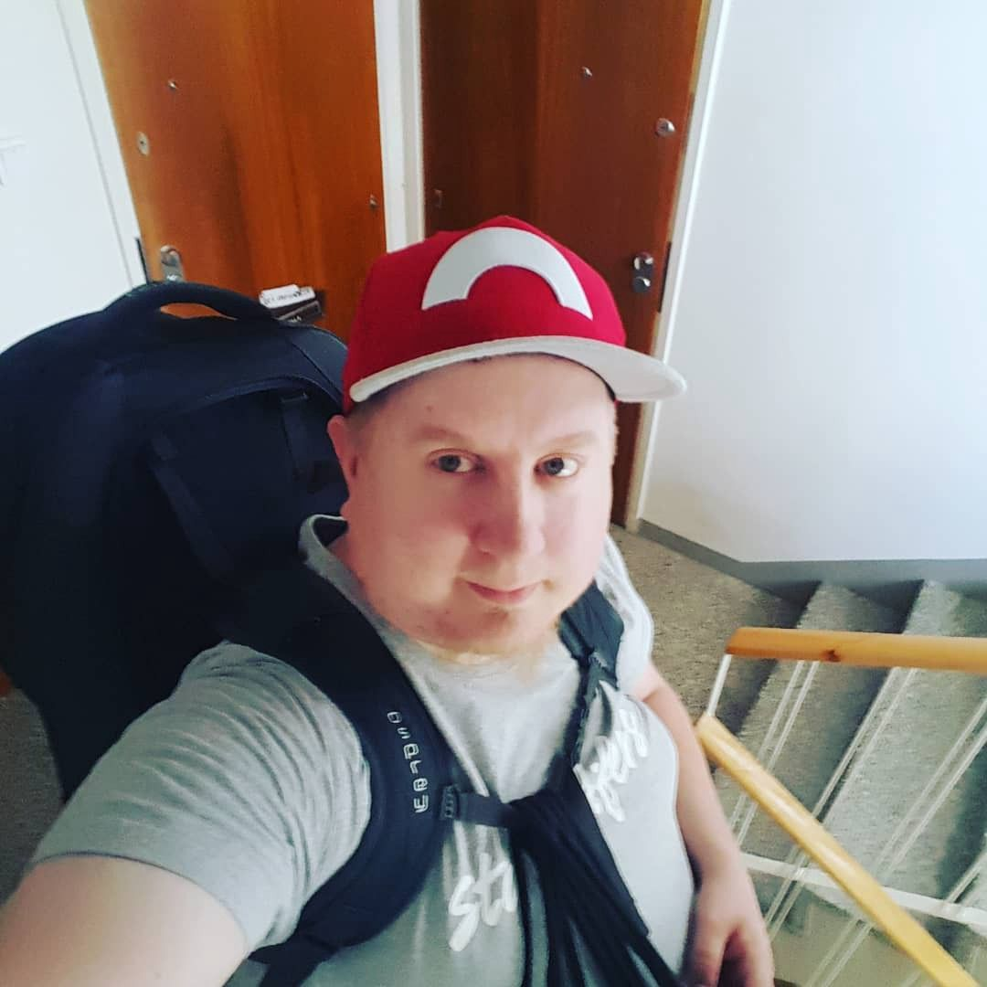 A selfie in staircase of me wearing a red cap and a backpack