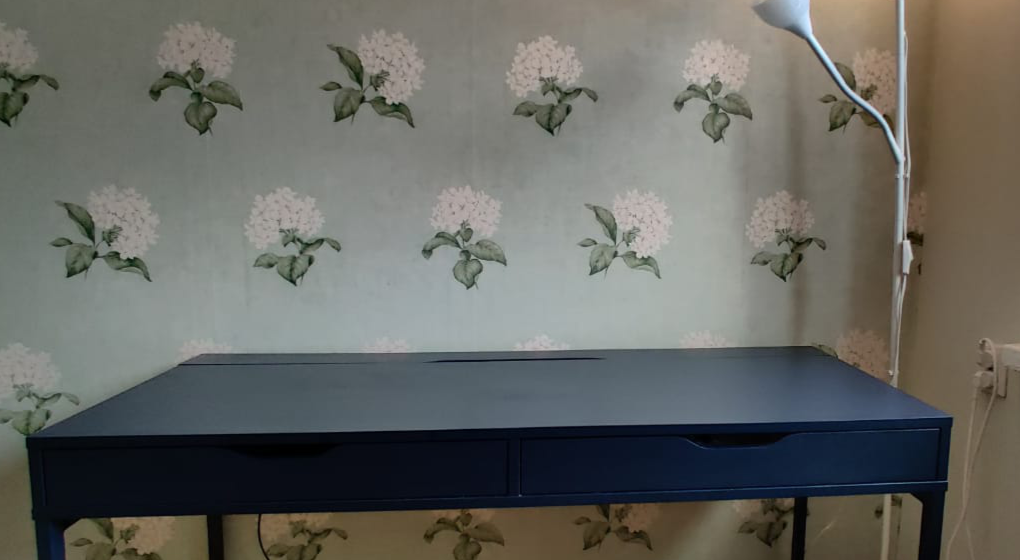 An empty desk with two drawers in front of a flower wallpaper
