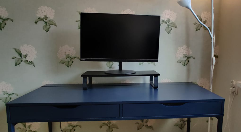 """A blue desk with a black display stand and a 27"""" ThinkVision display on top"""