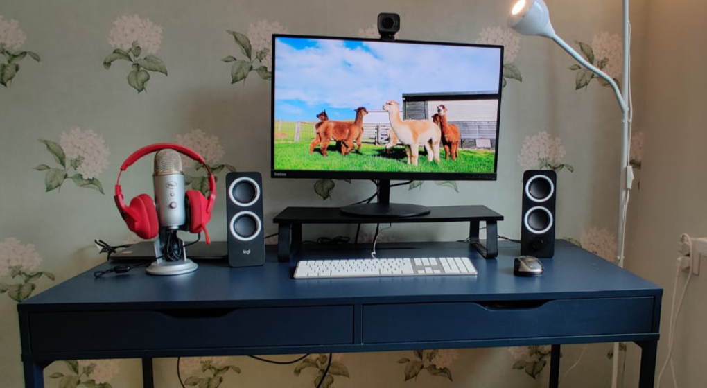 A desk with closed macbook connected to a display, white keyboard and black/grey mouse, small black standing speakers and a Yeti microphone with red headphones