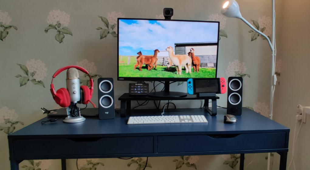 A desk with closed macbook connected to a display, white keyboard and black/grey mouse, small black standing speakers and a Yeti microphone with red headphones. A Nintendo Switch on one side of the display and Stream Deck on another