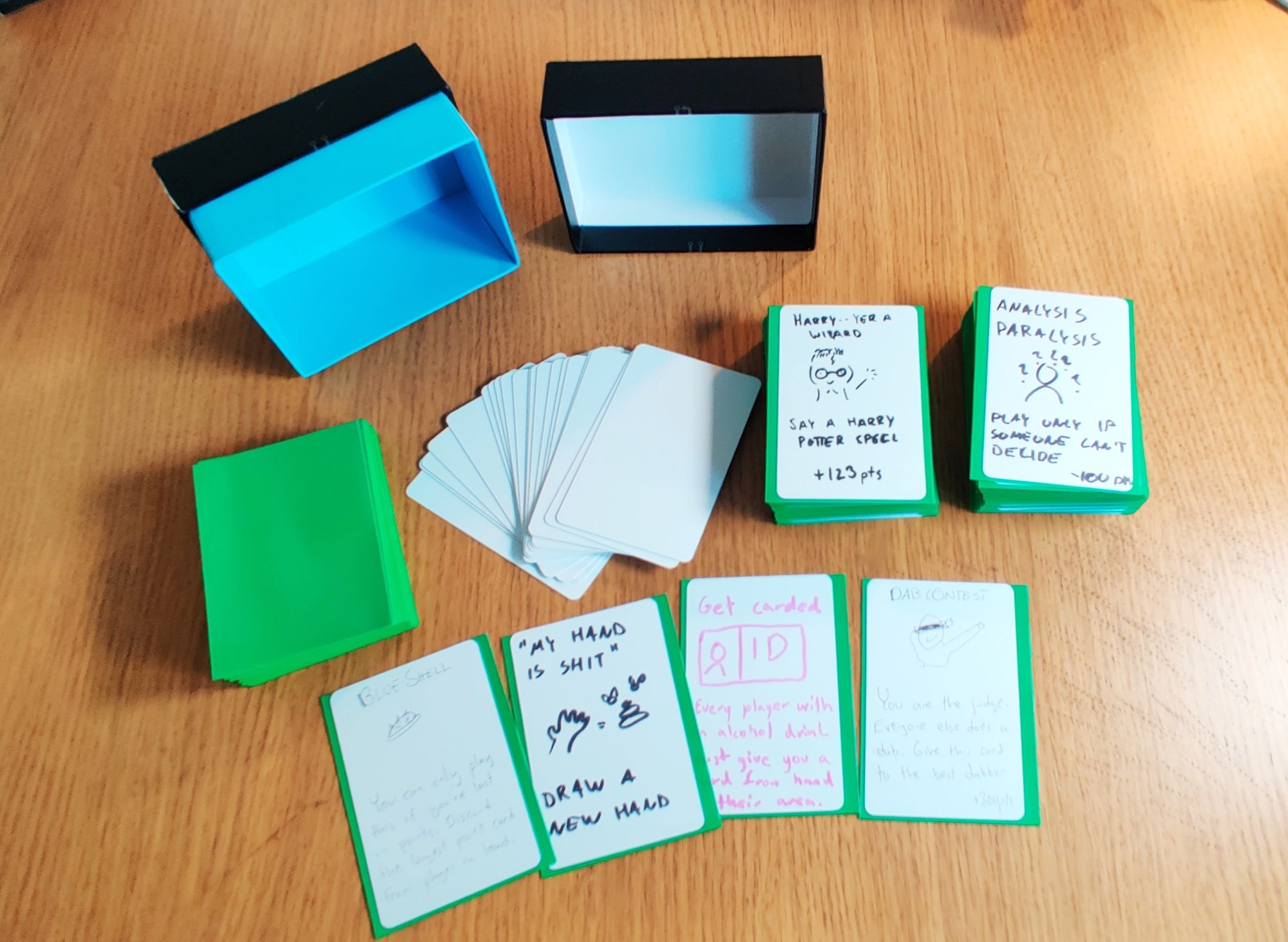 A collection of empty green sleeves, empty cards and two stacks of cards with handwritten text and pictures