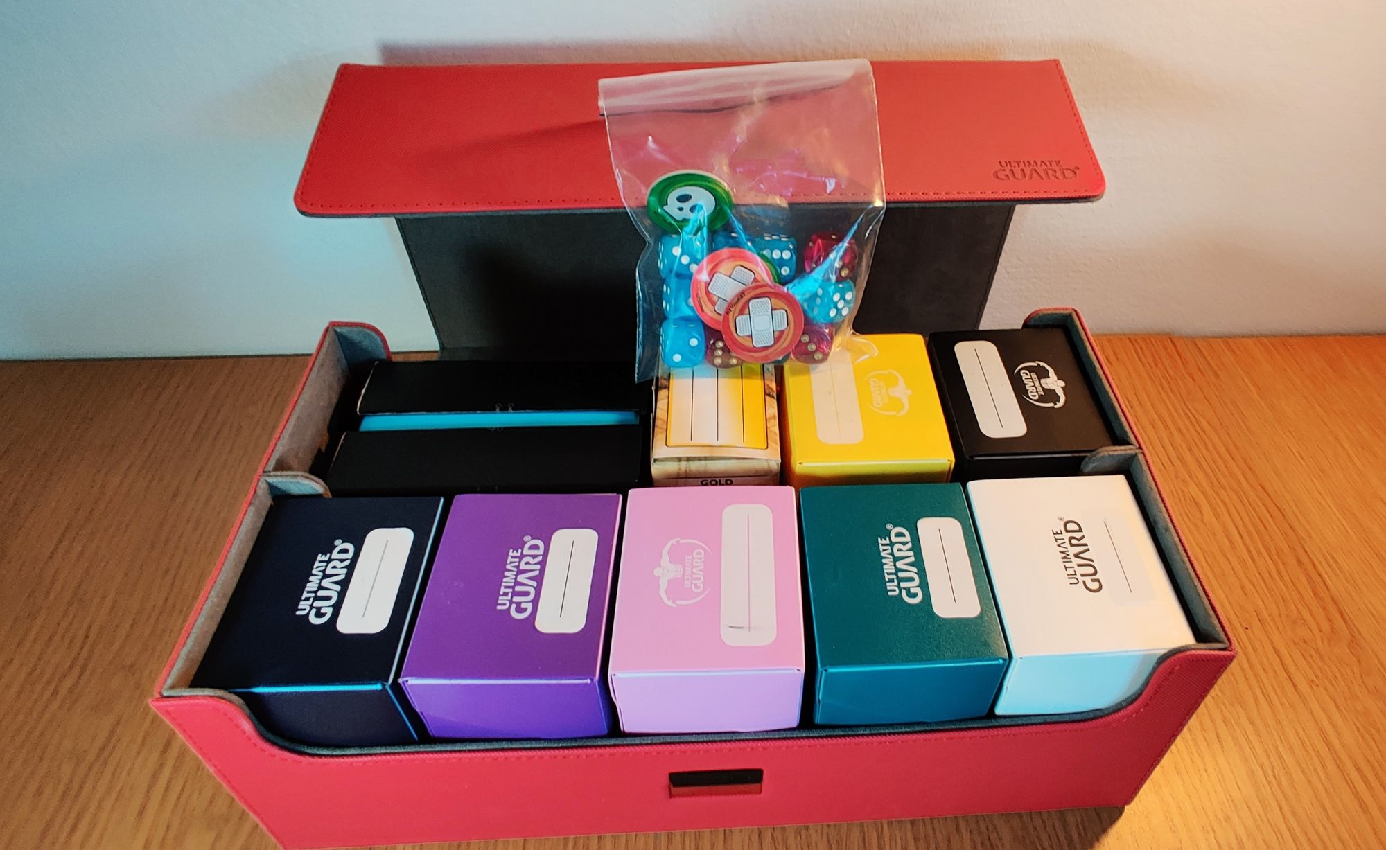 A large red box with open lid and 9 small deck boxes of games inside