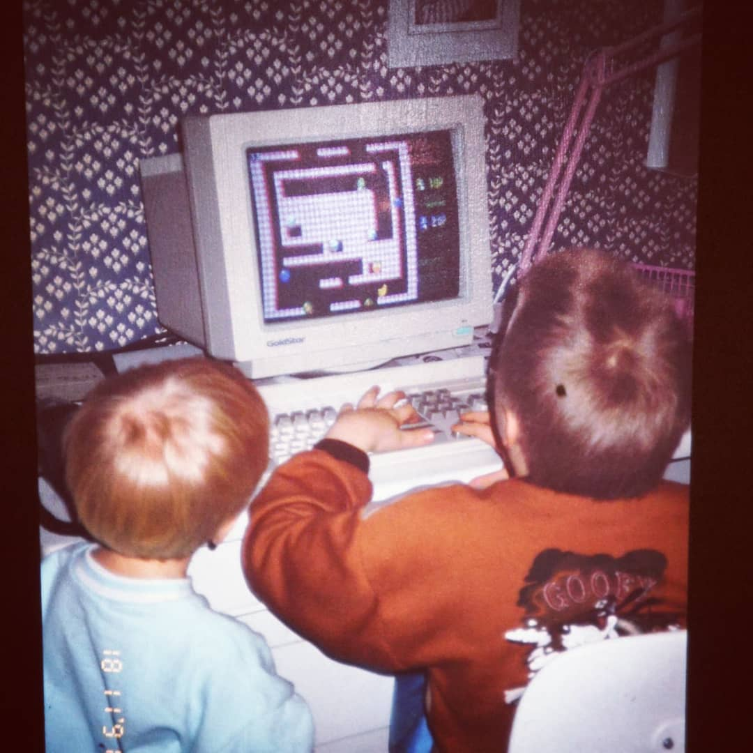 A picture from 1991, I'm standing next to my brother who's playing on a computer.