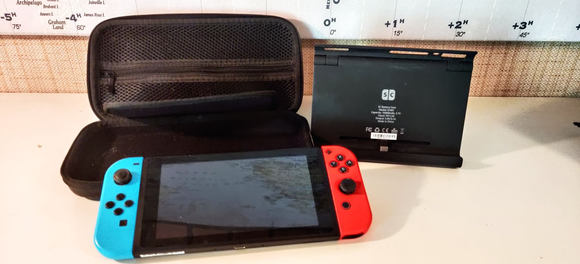 A Nintendo Switch next to a powerbank and a carrying case that's same size as Switch