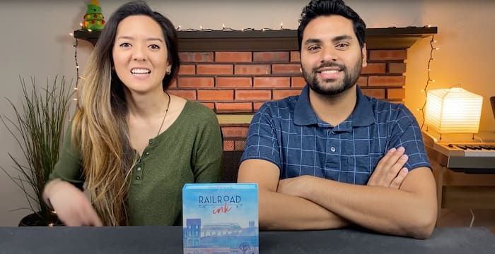A woman and a man sitting at a table, looking into the camera with Railroad Ink board game box in front of them