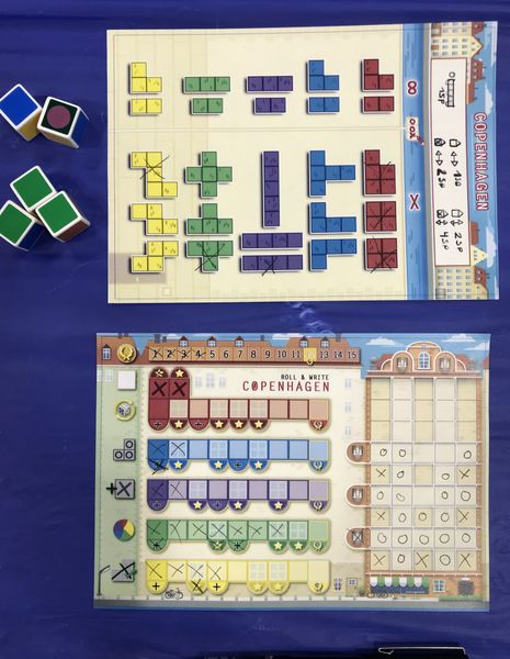 A board on top displaying different geometrical shapes and a bottom board with mid-game progress of Copenhagen