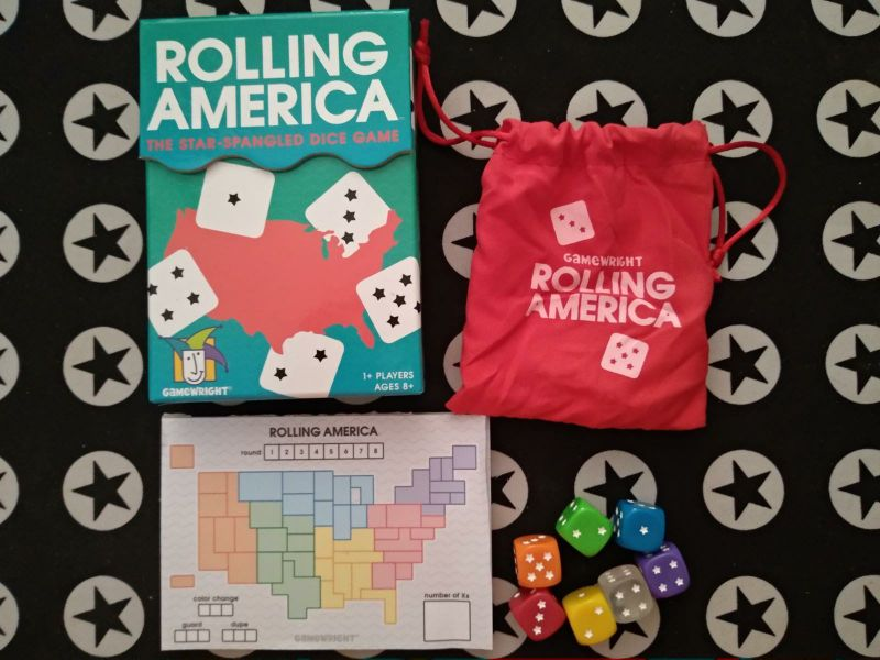 A box, a small cloth bag, 7 rainbow colored dice and a pad of game boards